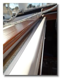 Down to the fiberglass on the port side of the companionway hatch
